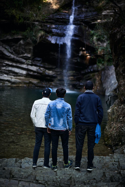man in blue jacket standing beside man in blue jacket near waterfalls during daytime