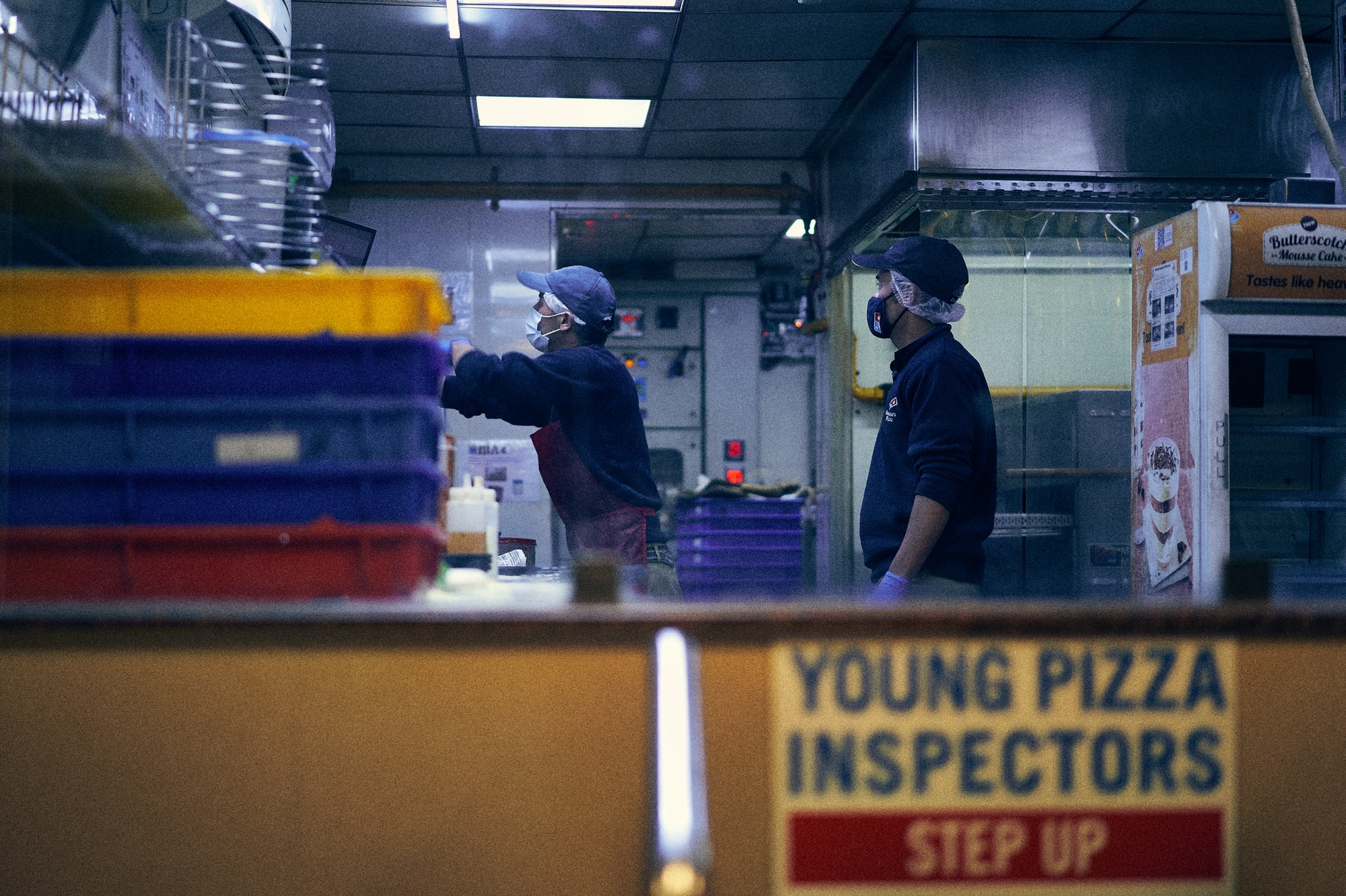 Two men wearing masks working at Domino's