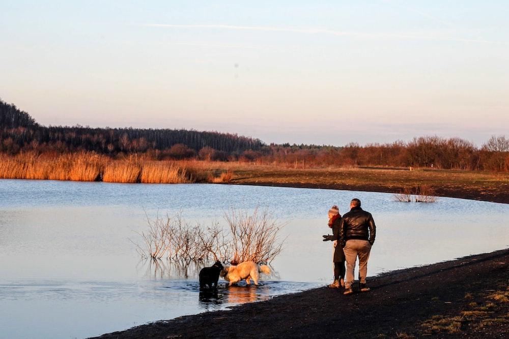 2 men standing on lake shore during daytime