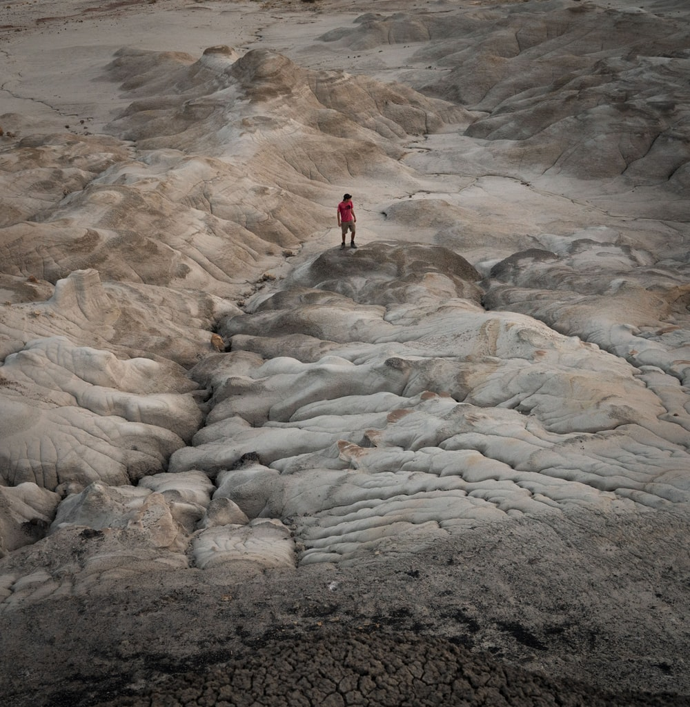 person in red jacket standing on rocky hill during daytime