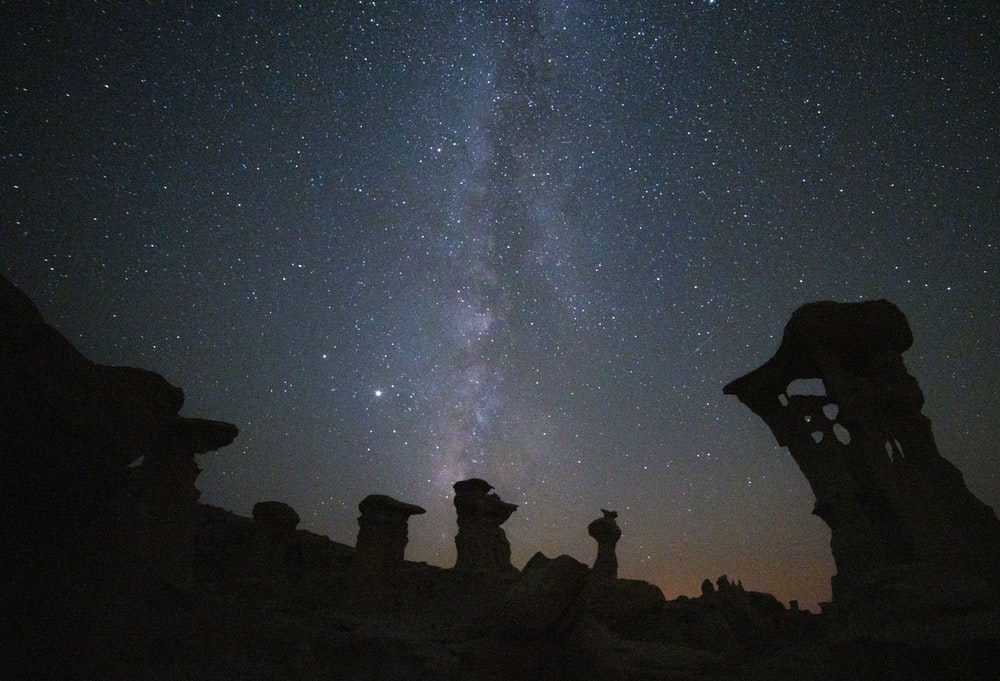 silhouette of people on rock formation under starry night