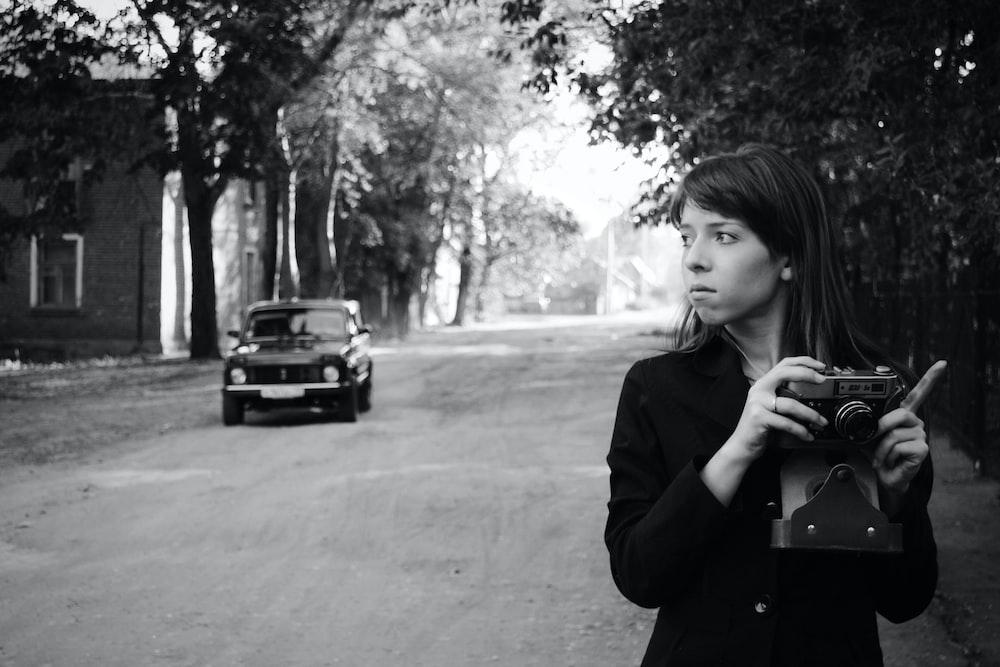 woman in black coat standing near black car