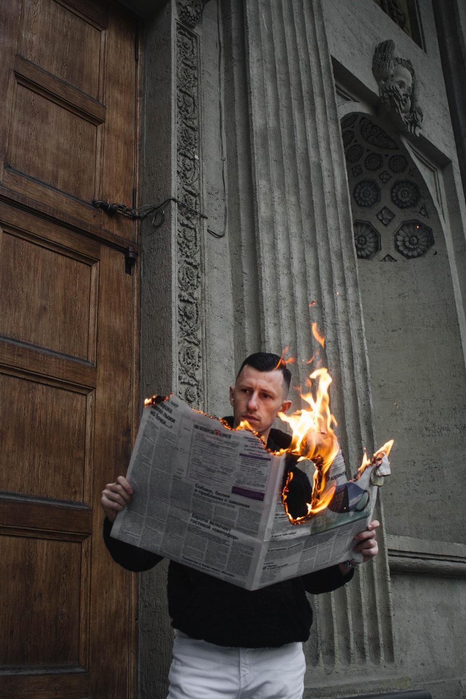 man in black jacket holding newspaper