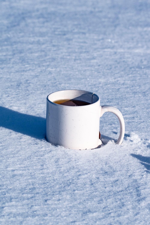 white ceramic mug on white snow
