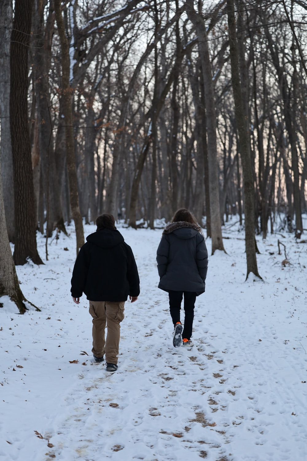 man and woman walking on snow covered ground during daytime