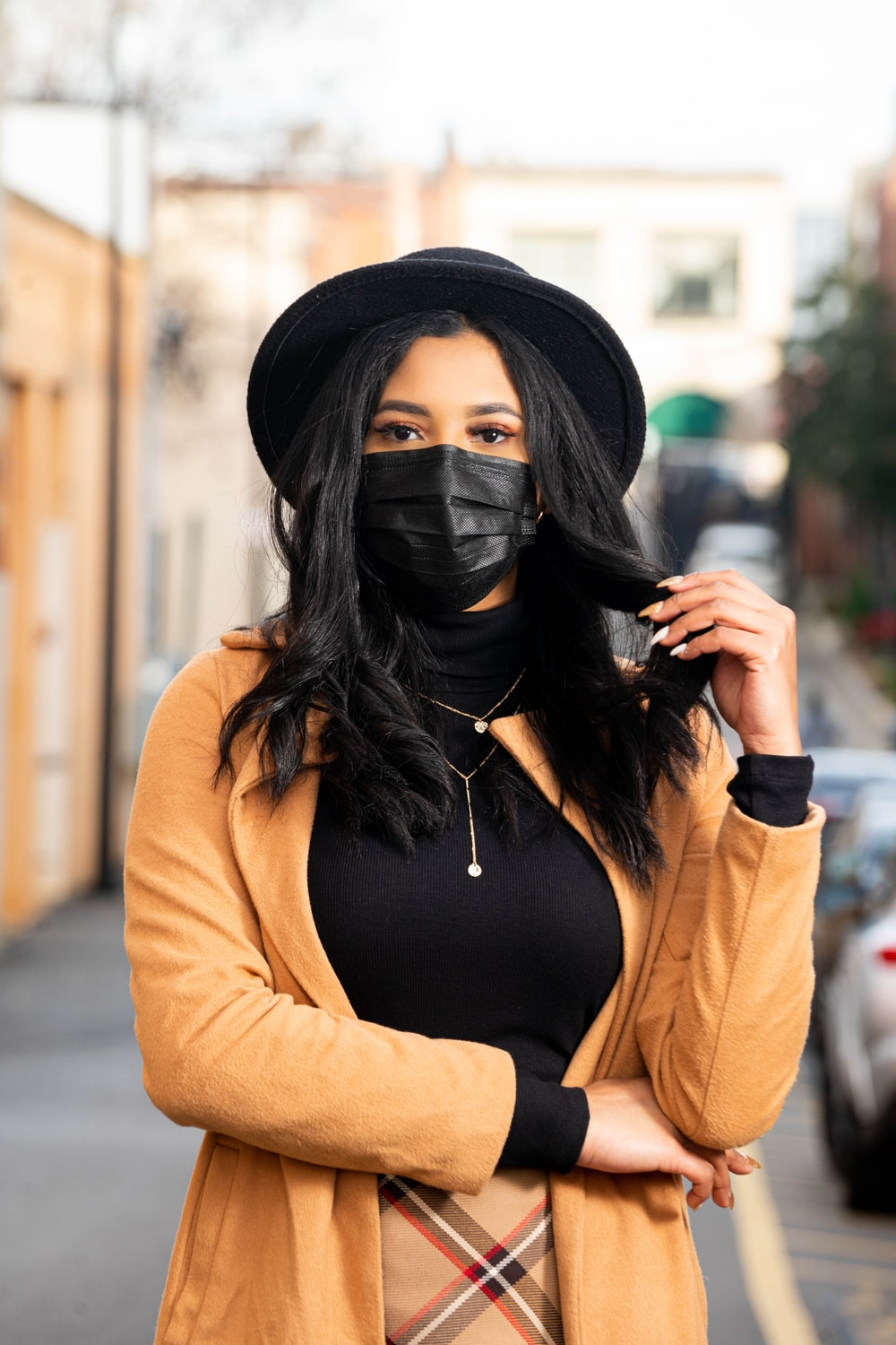 woman in brown long sleeve shirt covering face with her black hair