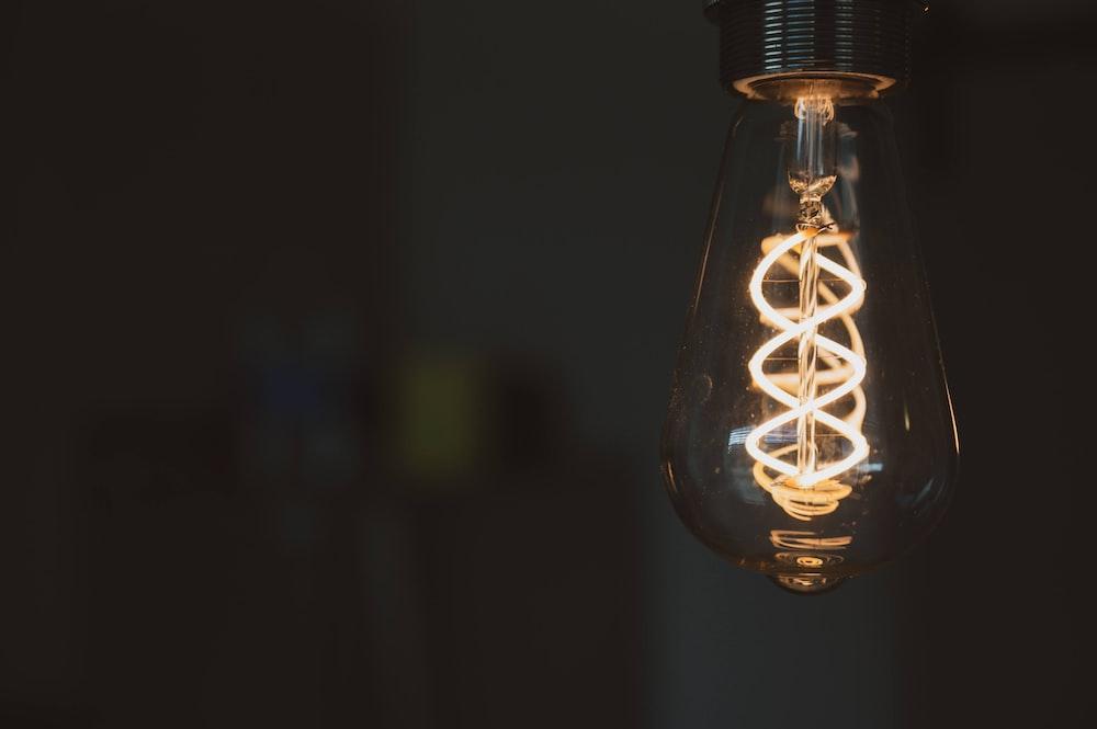 clear glass light bulb in dark room
