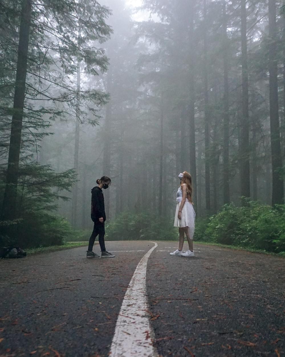 2 women walking on pathway between trees during daytime