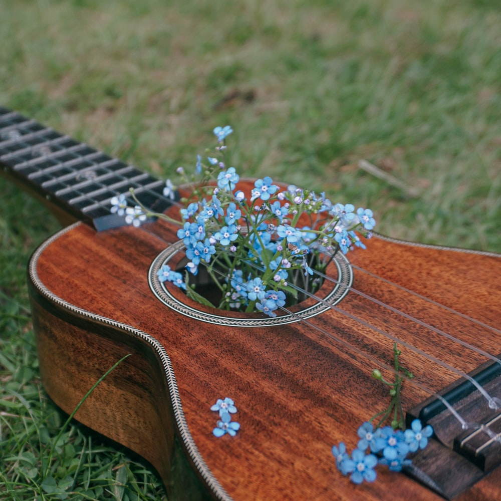brown acoustic guitar with white and green flower on top