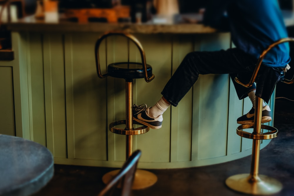 person in black pants and black and white sneakers sitting on bar seat