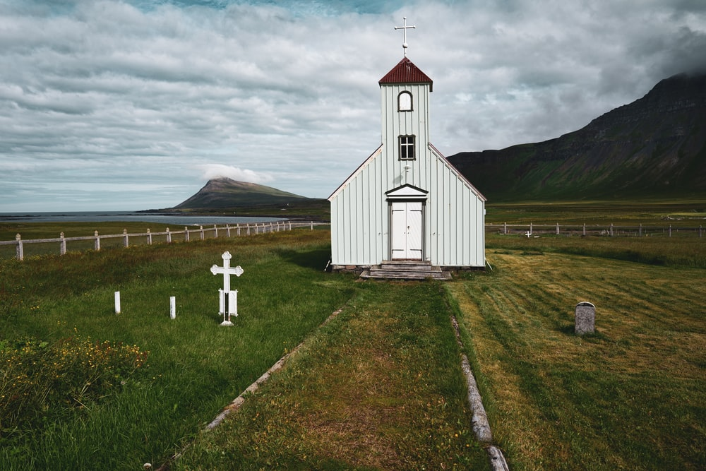 white wooden church on green grass field under white clouds and blue sky during daytime
