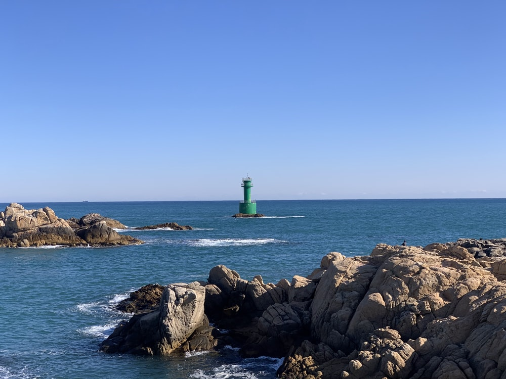 green lighthouse on rocky shore during daytime