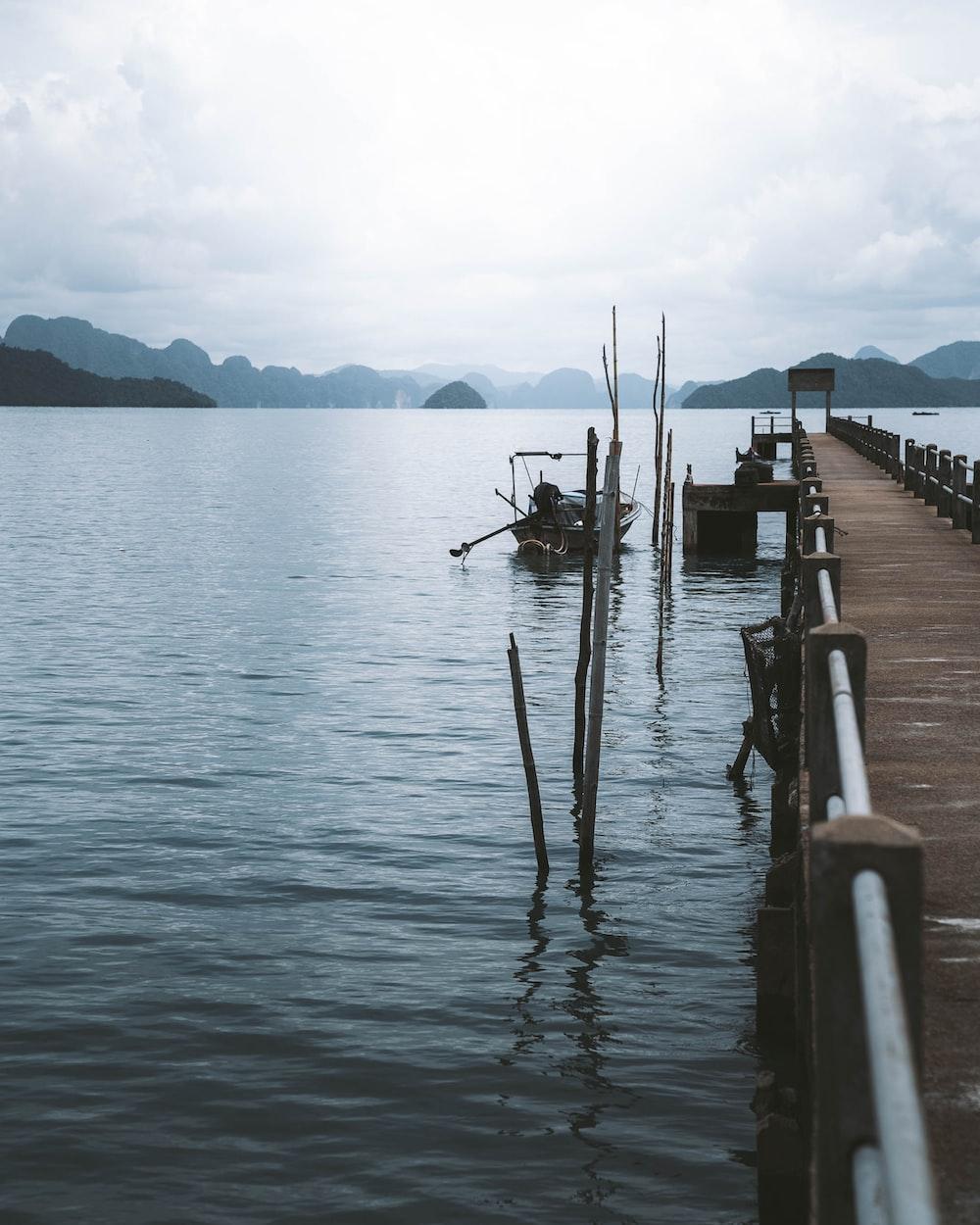 man fishing on sea dock during daytime