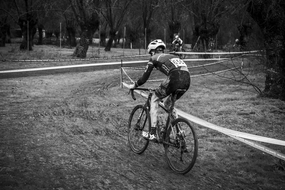 grayscale photo of man riding bicycle