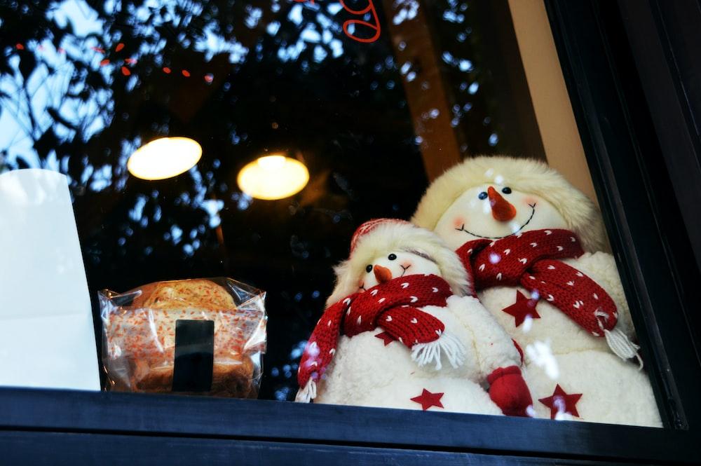 white snowman plush toy on glass window