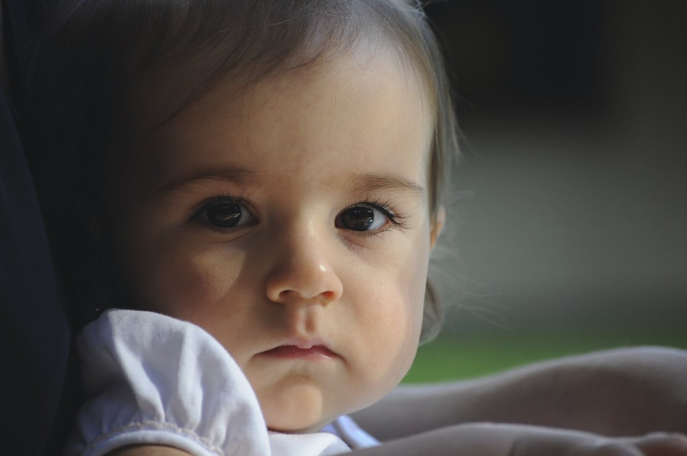 baby in white shirt lying on green grass during daytime