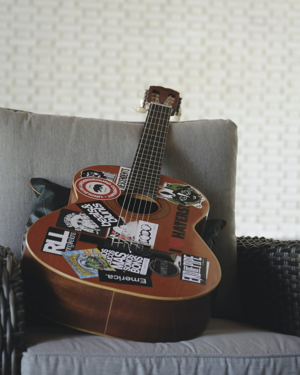 brown and black acoustic guitar on black and white textile