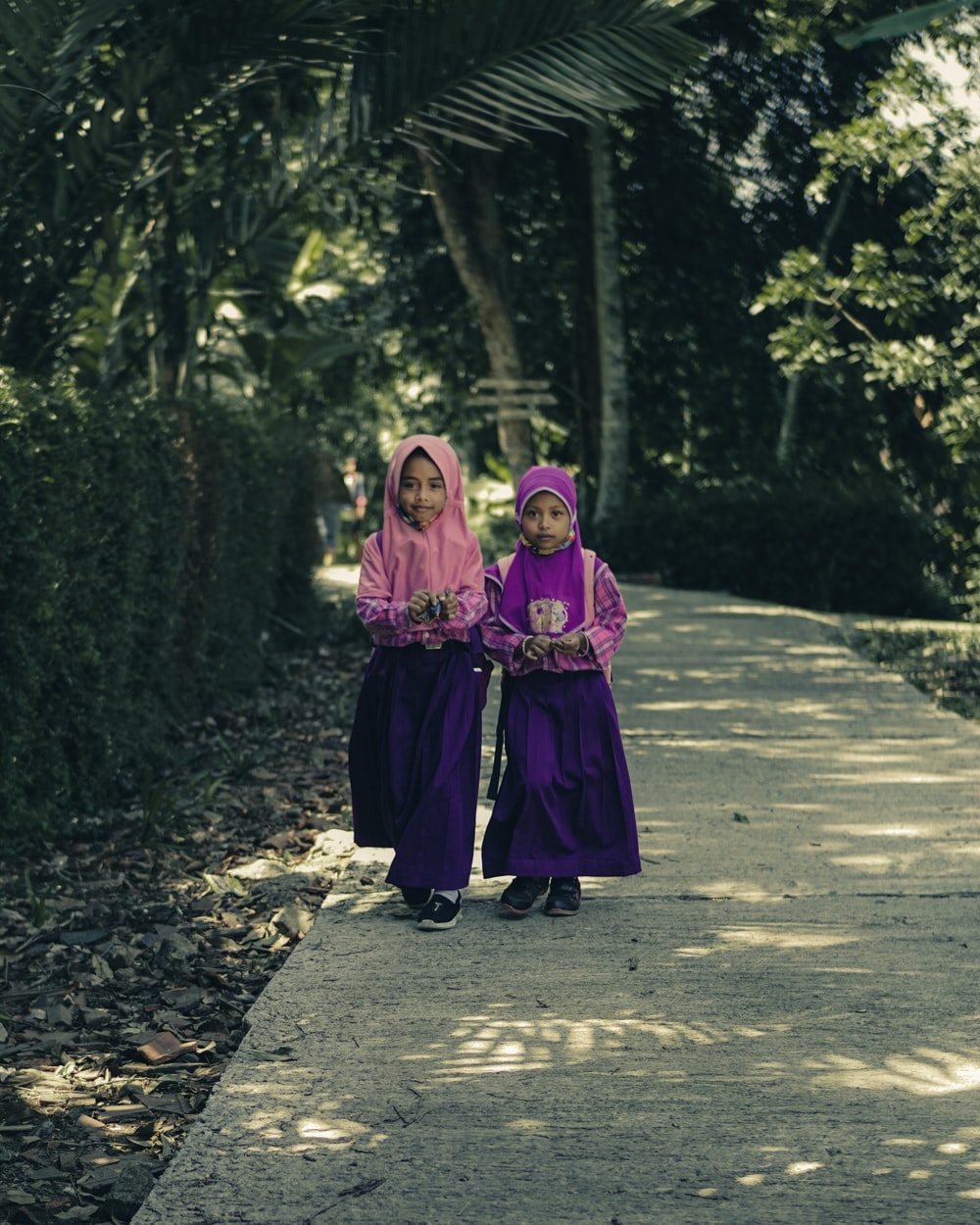 2 girls in pink and black dress standing on gray concrete pathway during daytime