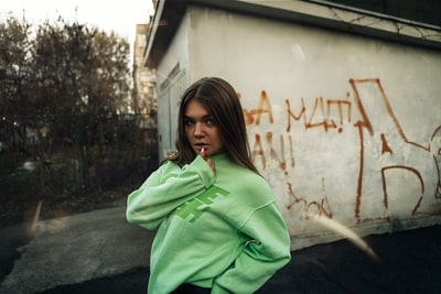 Galaţi woman in green hoodie standing beside white wall during daytime