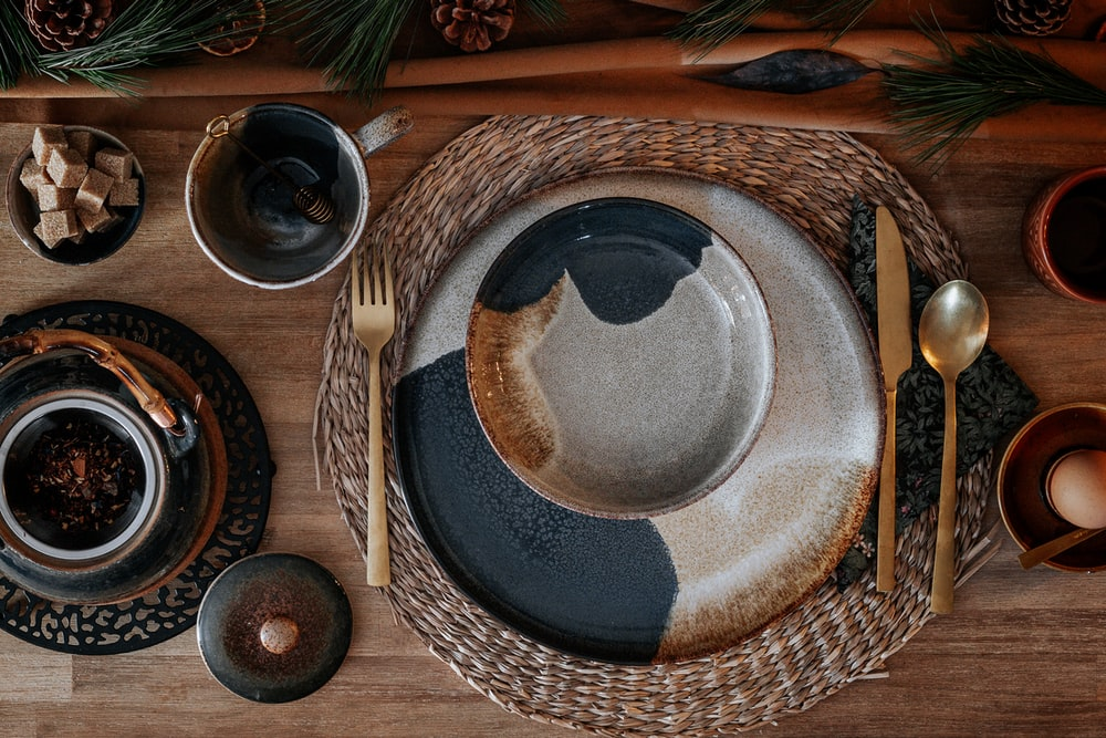 blue and white ceramic round plate on brown wooden table