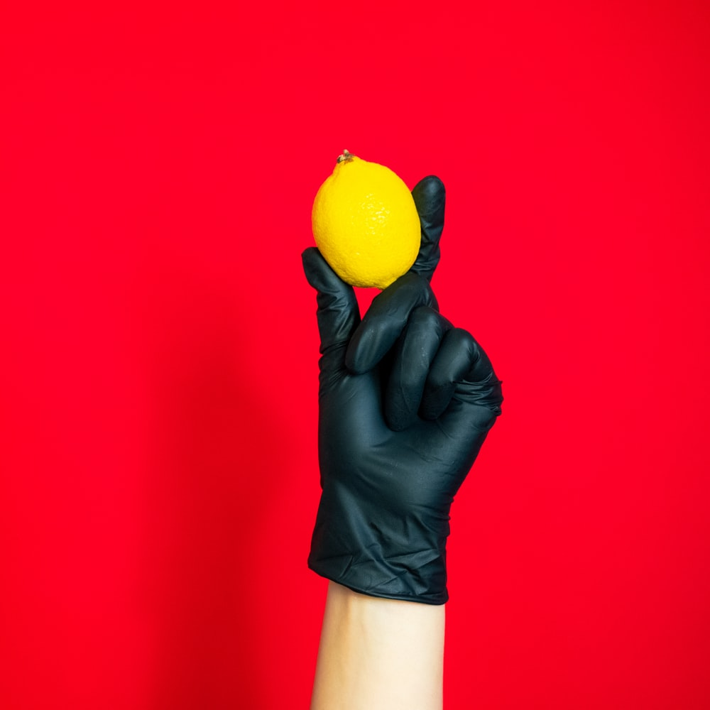 person holding yellow citrus fruit