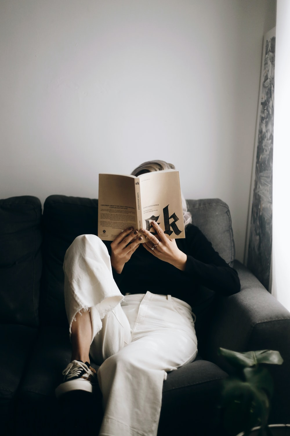 woman in white shirt reading book sitting on black sofa