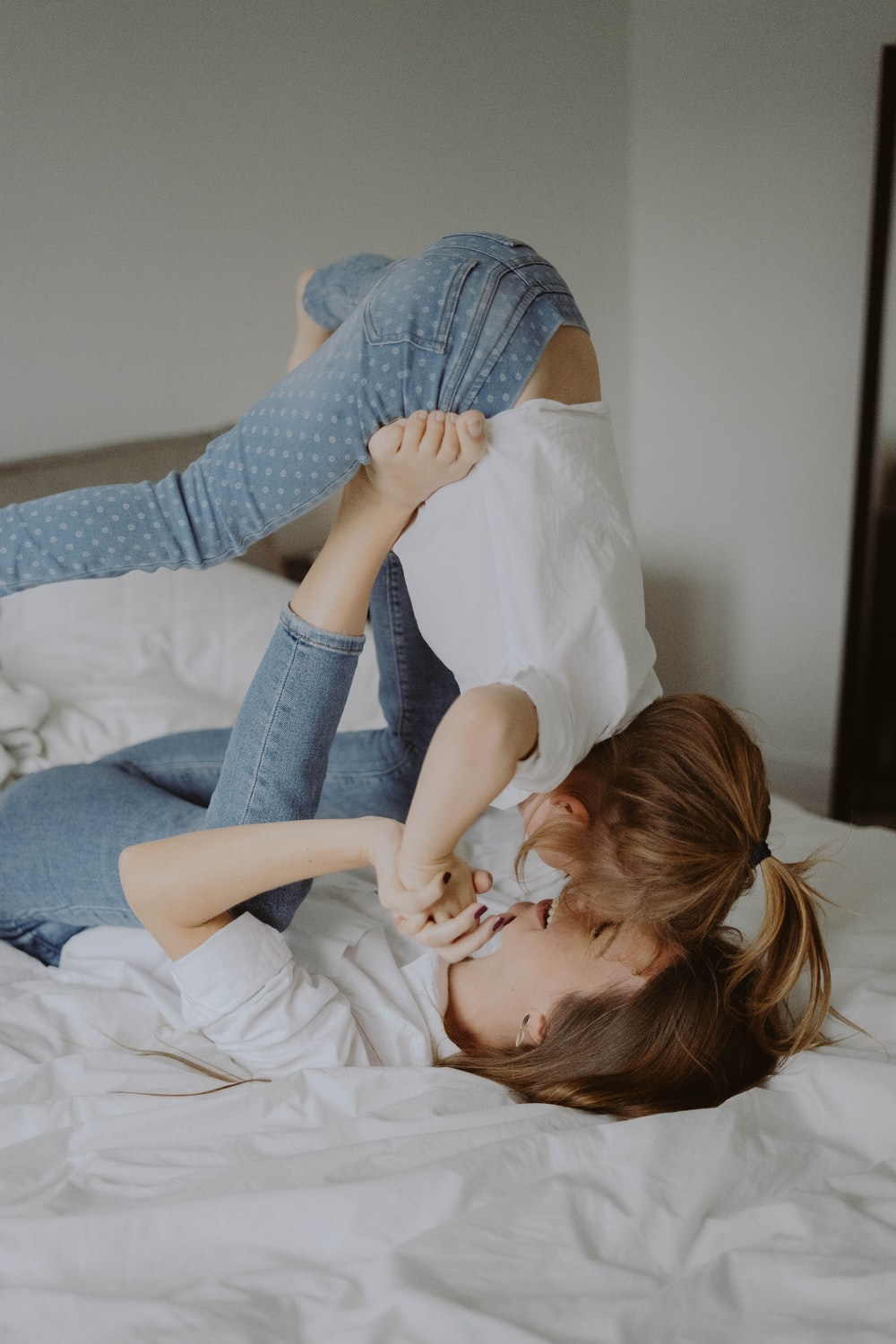 woman in blue and white polka dot shirt lying on bed