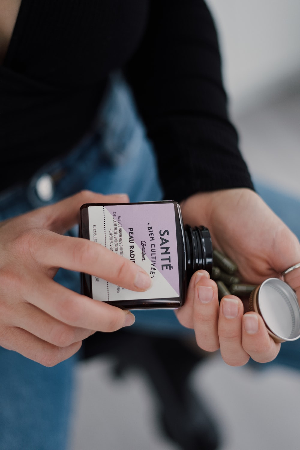person holding black and white labeled bottle