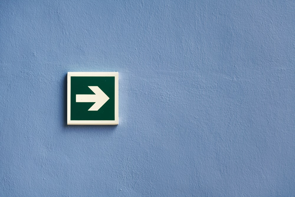 white and green arrow sign