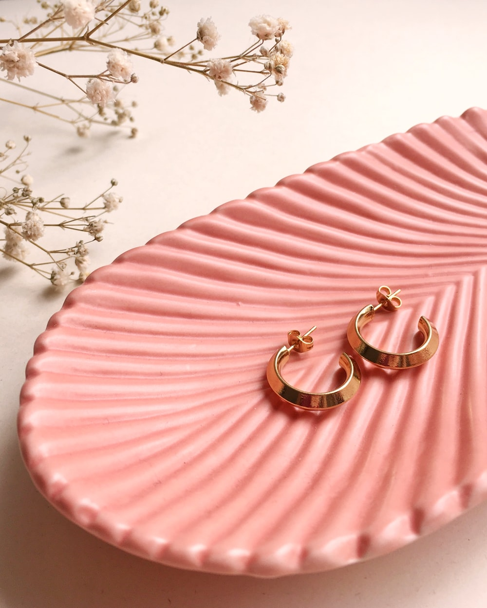 gold and silver rings on pink and white striped textile