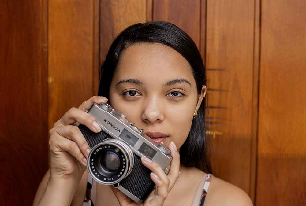 woman in white tank top holding gray and black camera
