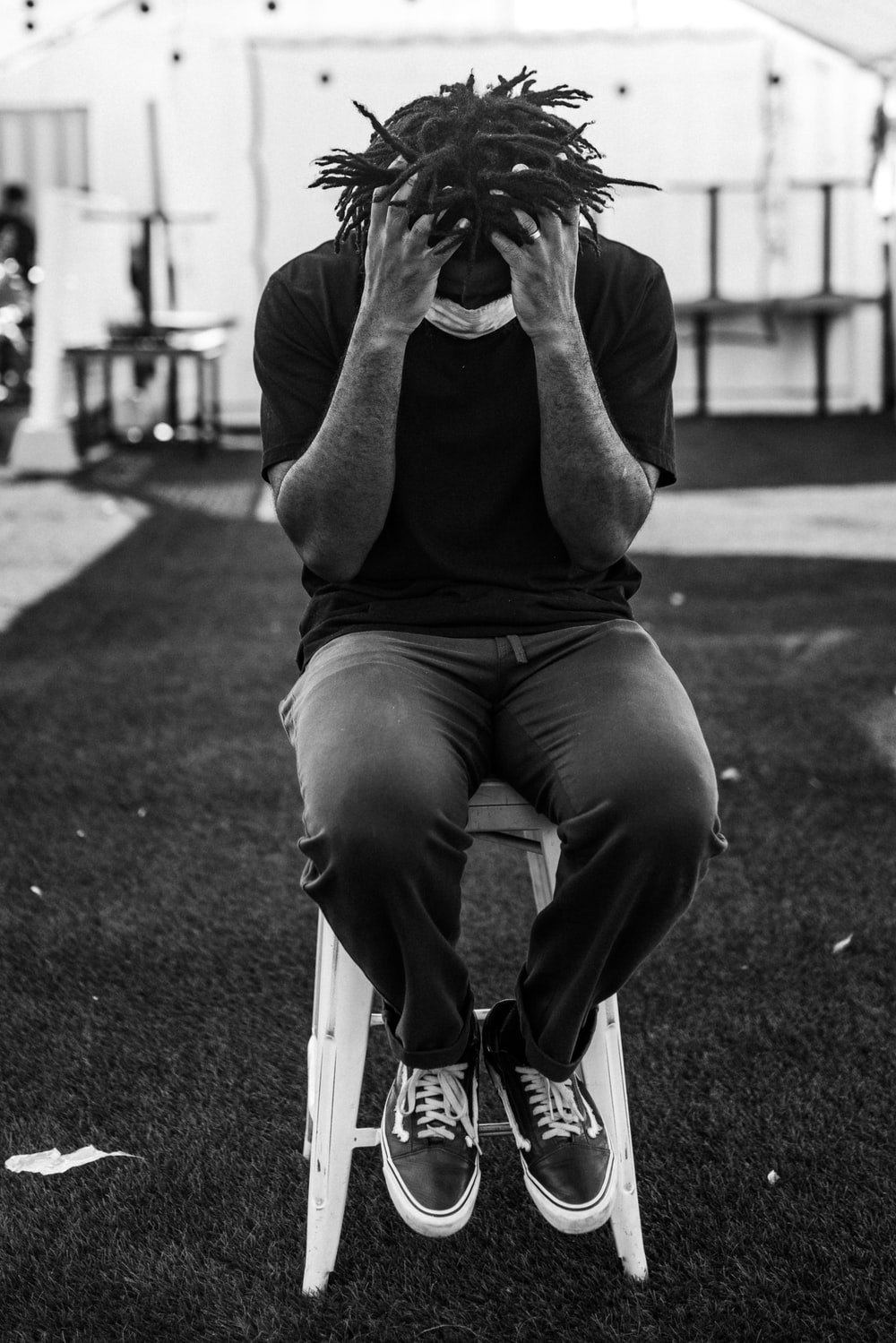 man in gray crew neck t-shirt and black pants sitting on concrete bench