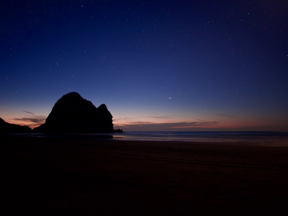 silhouette of rock formation on sea shore during night time