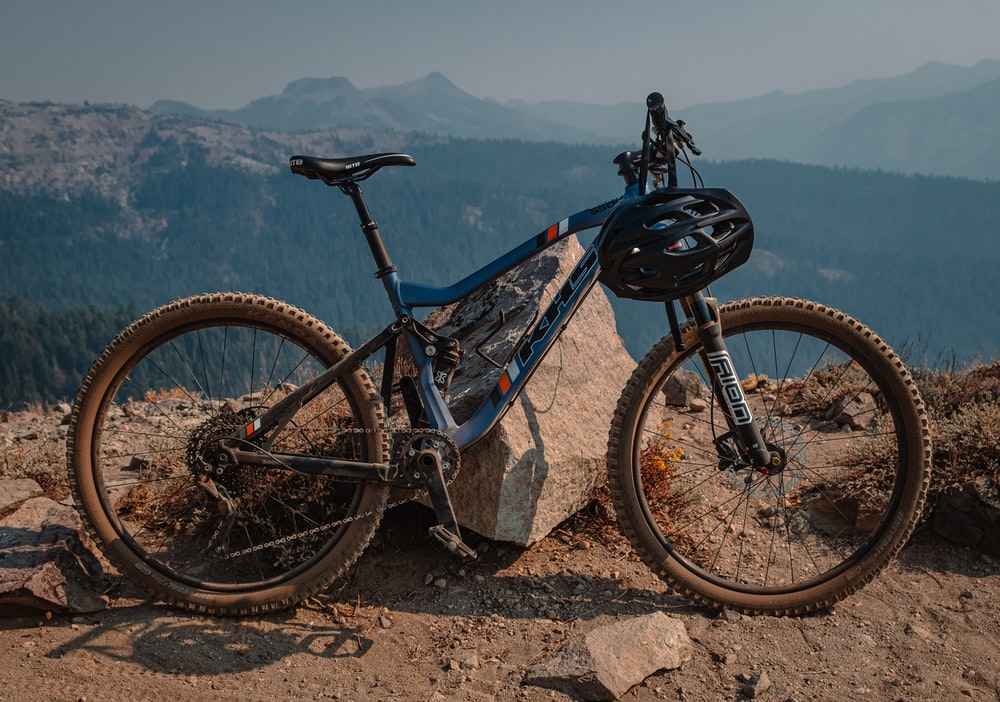 blue and black mountain bike on brown rock