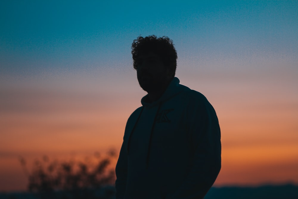 silhouette of man in black jacket during sunset