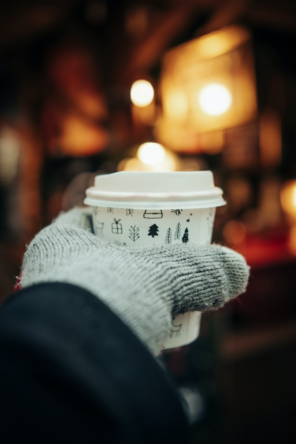 person in gray knit sweater holding white cup