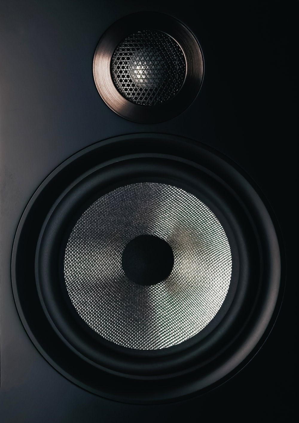 black and gray speaker on brown wooden table