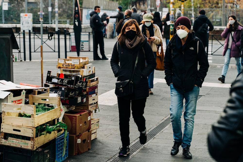 woman in black jacket and blue denim jeans walking on sidewalk during daytime