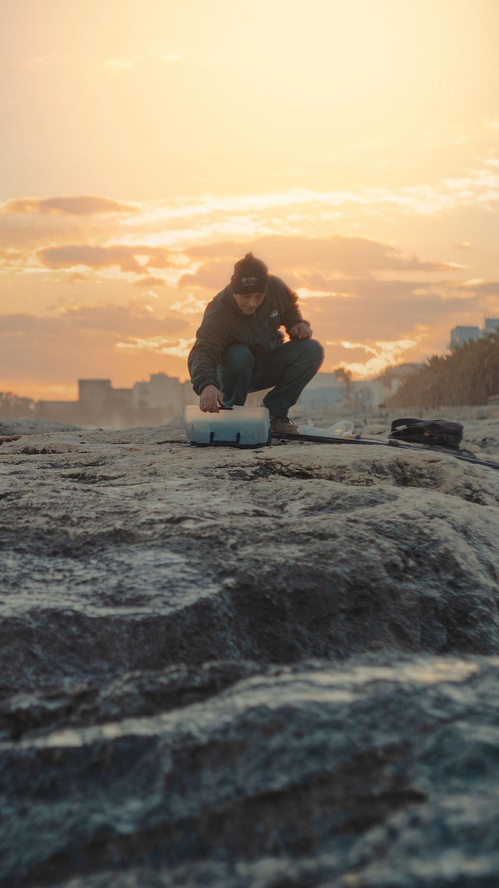 man in black jacket sitting on rock