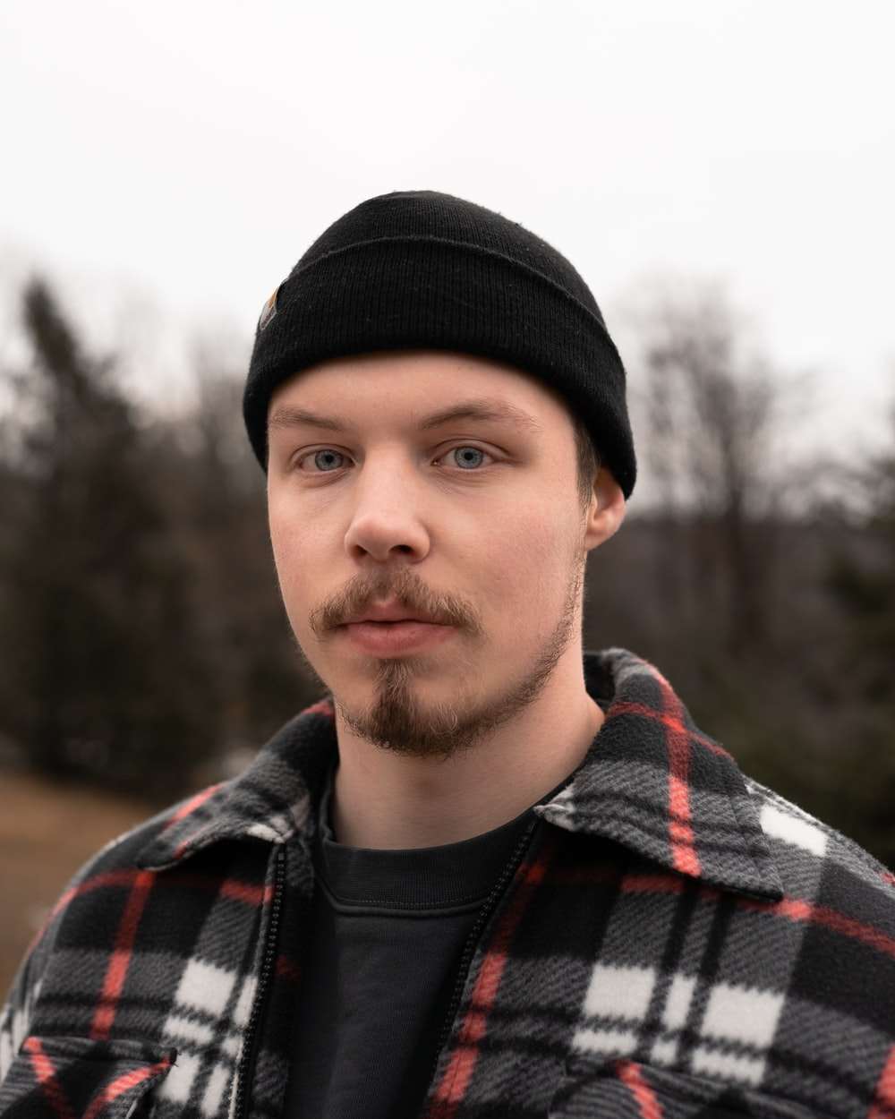 man in black knit cap and black red and white plaid jacket