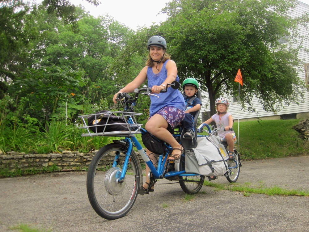 3 women riding on blue bicycles during daytime