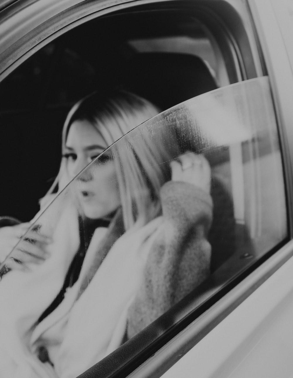 woman in white coat in car