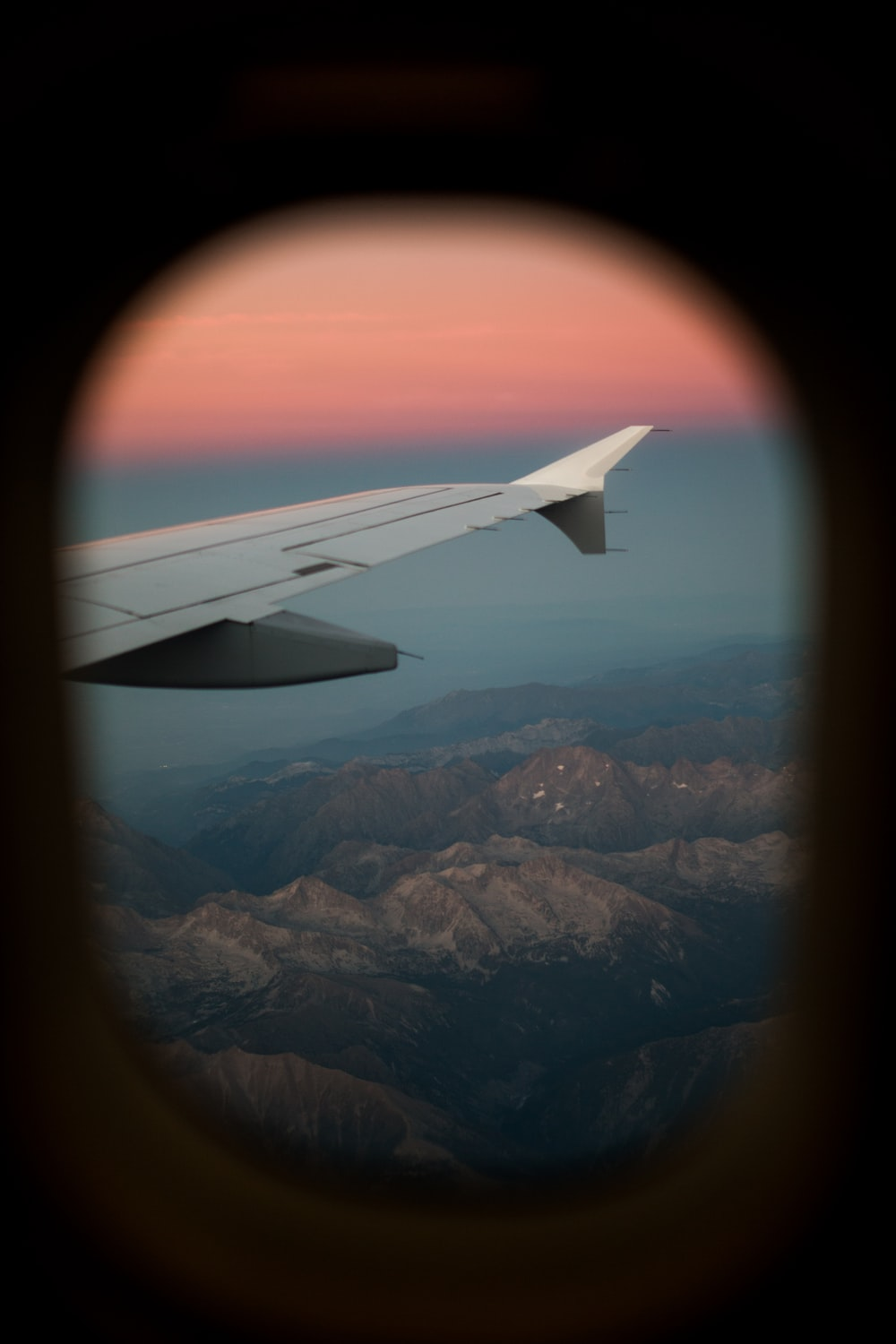 airplane window view of mountains during daytime