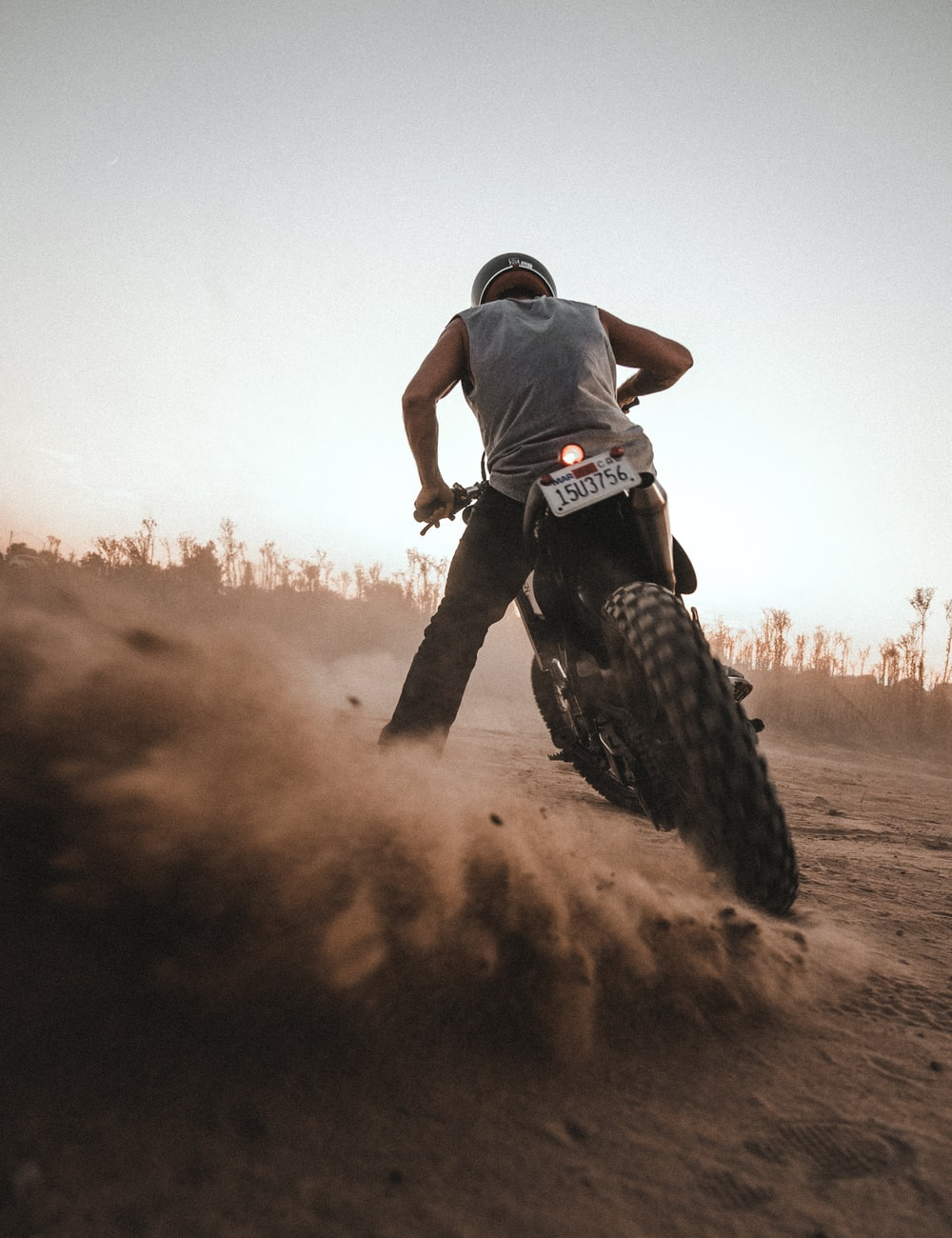 man in black t-shirt and black pants riding motocross dirt bike on brown field during