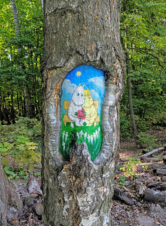 blue and green bird graffiti on brown tree trunk