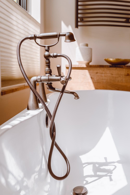stainless steel shower head on bathtub