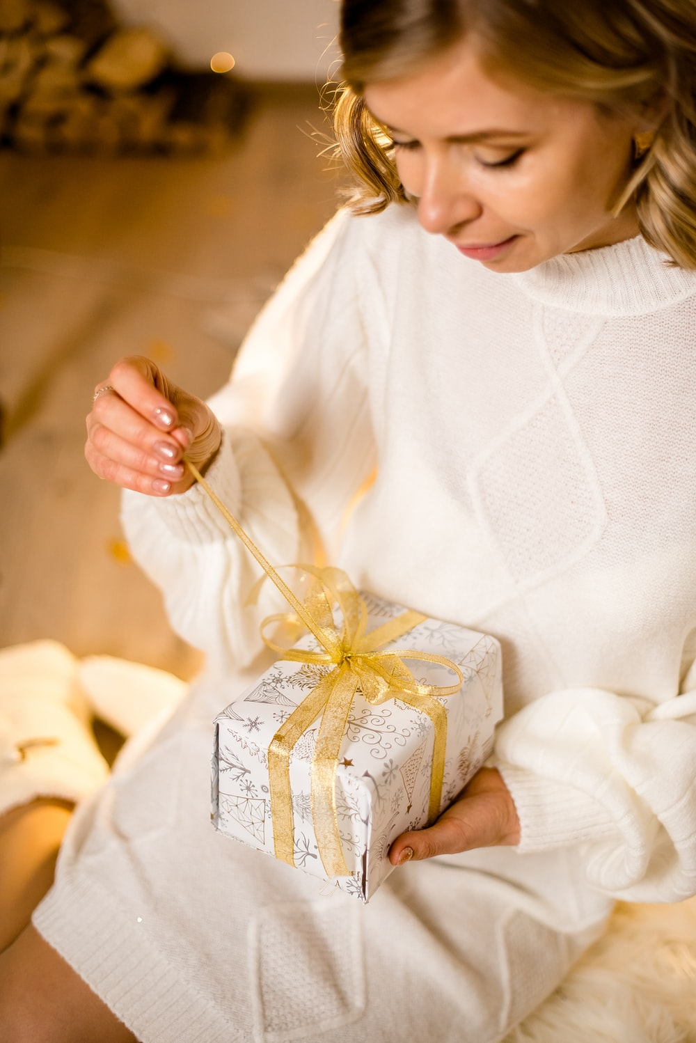 woman in white long sleeve shirt holding white and blue floral gift box