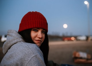 woman in gray hoodie wearing red knit cap