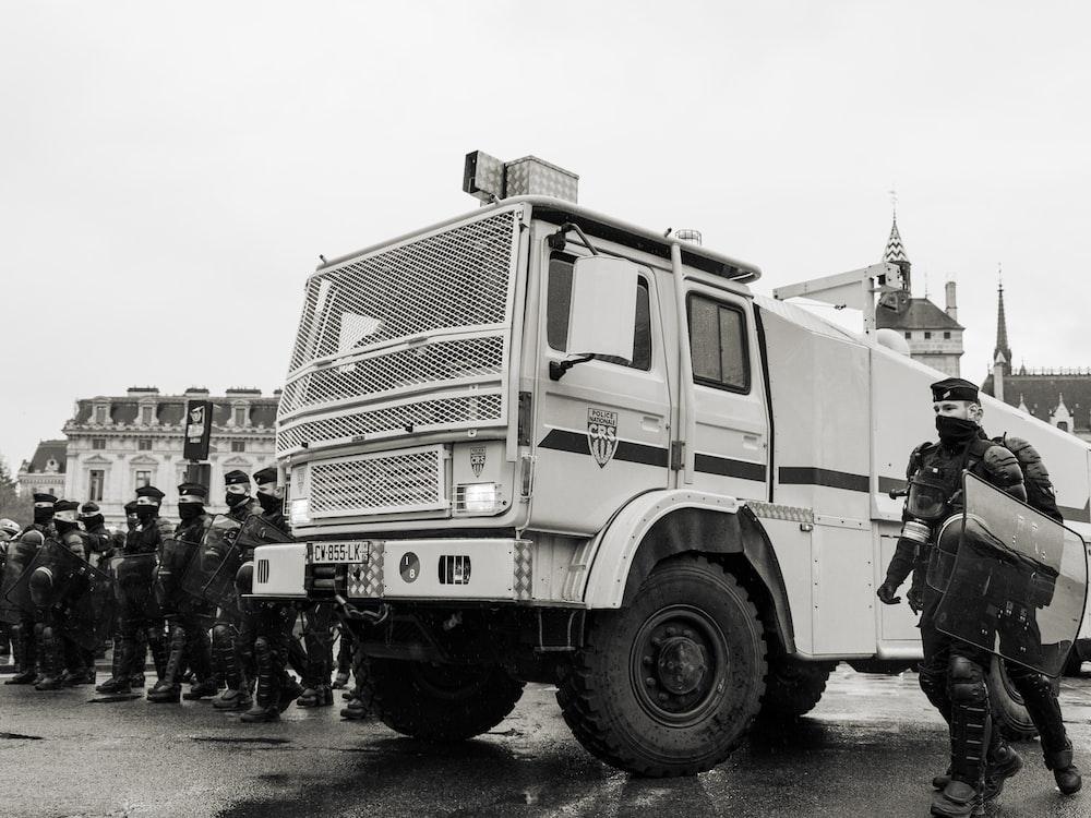 group of men standing beside white truck