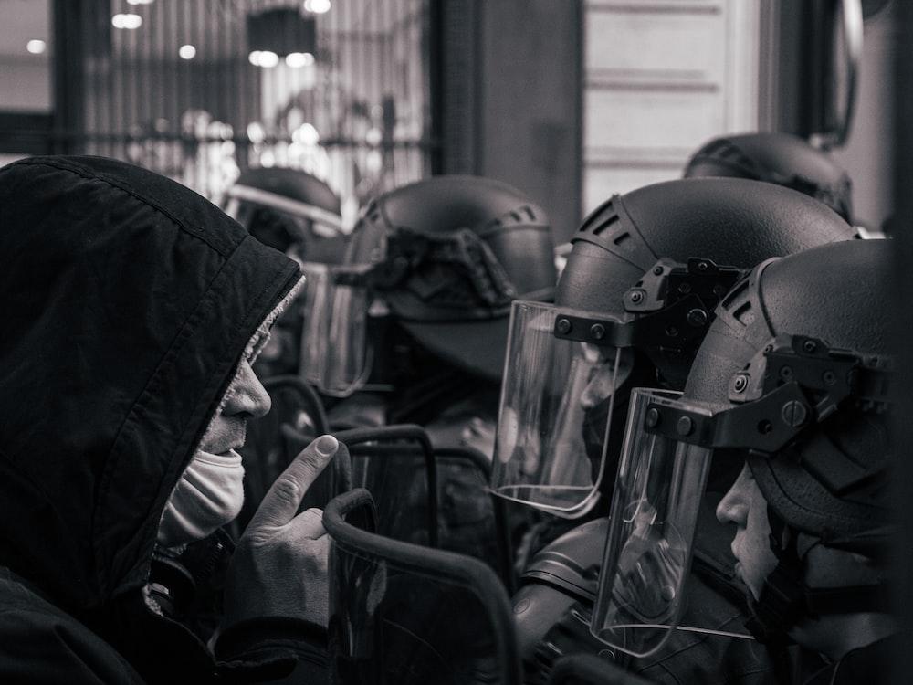 grayscale photo of motorcycle helmet and helmet